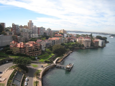From the north end of the Sydney Harbour Bridge sidewalk, this view of homes is typical of everything near downtown, with the ground rising from the water and many floors of many buildings soaking up the sun and views.