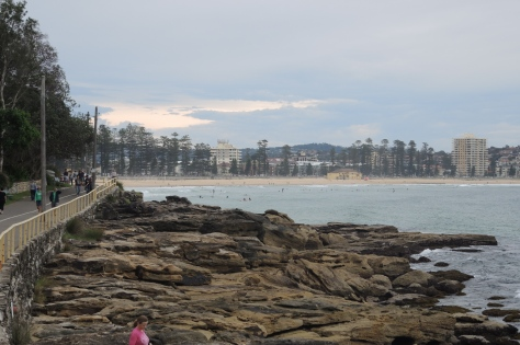 Manly Beach is the town and the sandy ocean face, a small line of pines, a walkway to explore, and a bustling Saturday marketplace.
