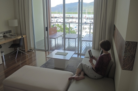 Betsy enjoys a book by the sea from the couch of our modern Cairns hotel room.