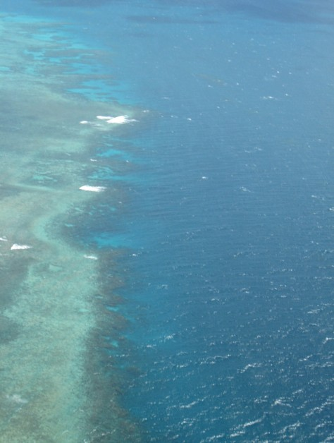Spectacular helicopter views of one reef, Bat Reef, in the Great Barrier Reef. Shallow reef, left, gives way to waters of greater depth and deeper blues. White areas are wave breaks onto the reef, just as they might on shore.