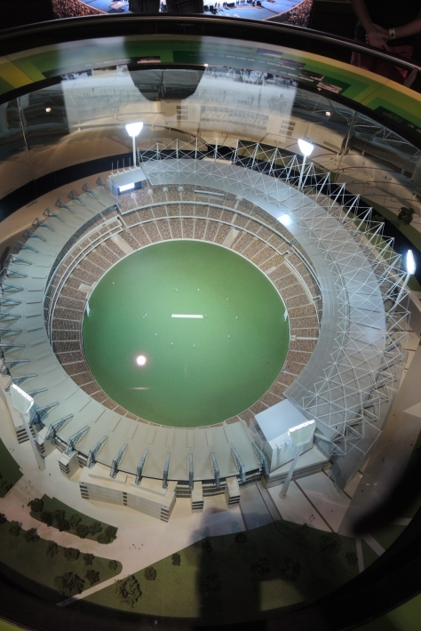 This scale model about 6 feet across shows MCG as if we had an aerial view.  The on-field white dash is the 22-meter (68-feet) pitcher-batter space for a game of cricket.