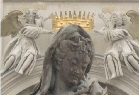 Laying a crown on Mary's head.