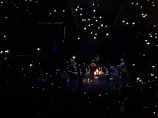 Justin Timberlake and crew around a campfire on the far stage